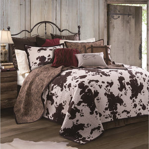 Make your country house cozy with this cowhide printed quilt set. The reversible quilt has a back of paisley printed chocolate, while the front has a whimsical dark russet and chocolate cowhide print. Standard pillow shams are quilted on the paisley print side; the cow print side is unquilted.