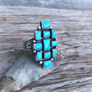 Queen of the Southwest  The Stones: Gorgeous bright blue Sleeping Beauty turquoise setting with 11 genuine carved Sleeping Beauty stones measuring 5x7 to 9x7mm in sterling silver.  The band: Handmade by silver-maker in .925 Sterling Silver this custom wide band has vintage Southwest / Navajo detail.  Made in size 9 / R this exquisite ring will fit most ladies fingers. Statement size 35x23mm. New Mexico Artisan. Stamped.