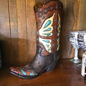 "Add a touch of western romance to your rooms interior  Beautiful vase replicates a brown tooled leather boot with beautiful Turquoise detail.  Display on its own or with a rustic dried arrangement. Options are endless.  Boot Vase (Inches): Adorned with a fun, fanciful design, the resin Turquoise Cowboy Boot Vase holds your artificial flowers with western style. Measures approximately 14"" X 9"" X 3"". Not intended for use with water."