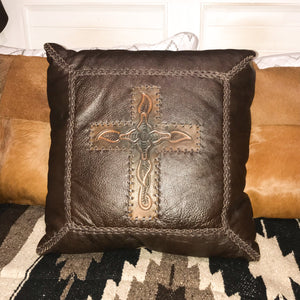 "Country luxe furnishings   Add a touch of leather luxe to your homes interior with this Lexington Cushion. This cushion is all Western with its dark chocolate leather, embossed motif cross centre piece and buck-stitch detail.  Generous 18""x18"". Pillow is crafted from 100% leather, filled cushion.  Dry clean only. Sourced by us from Dallas TX. Handcrafted in Mexico"