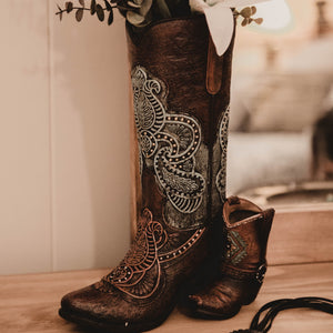 "Add a touch of western romance to your rooms interior  Beautiful boot vase decor. This beauty is 12"" tall and replicates a brown vamp tooled leather boot with beautiful blue detail.  Display on its own or with a rustic dried arrangement. Options are endless."