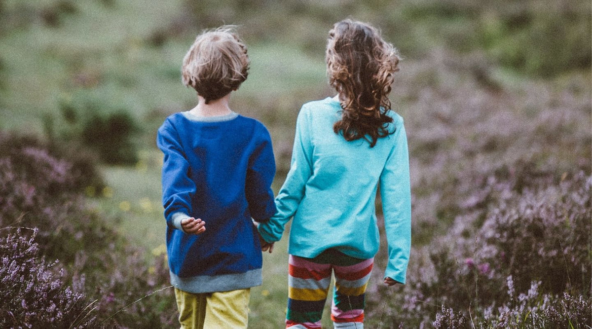 Two children walking in nature holding hands
