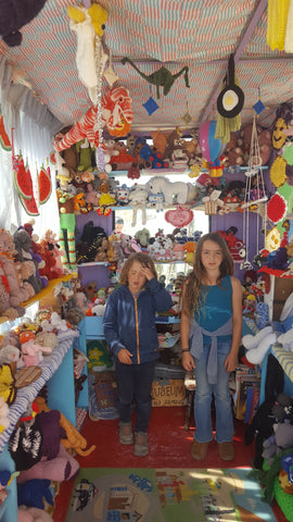Two children standing in a small room surrounded by crocheted objects at the Crochet Museum in Joshua Tree