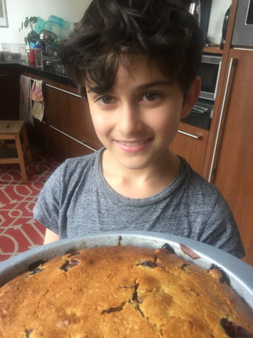 Child holding a cake with a smile on his face and tired eyes