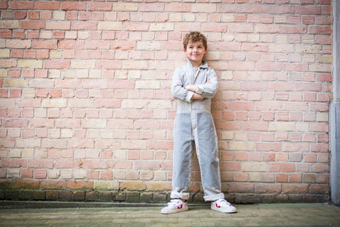 Boy with arms crossed wearing the Mac coverall in Engineer's Stripe, he's standing against a brick wall.