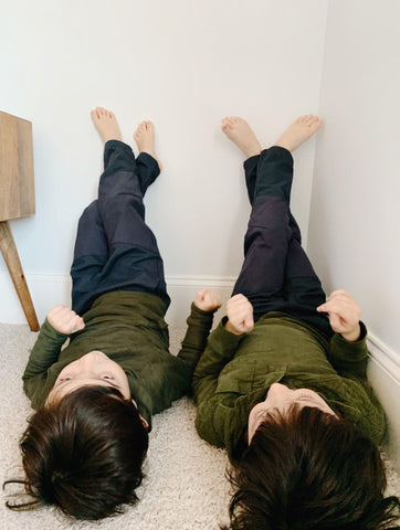 Two kids laying on the grown with their legs up the wall, wearing Jackalo.