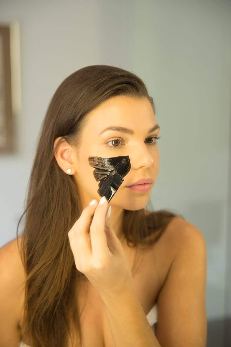 Apply your activated charcoal + coconut mask with the brush