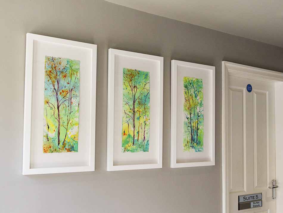 Triptych of tree paintings hanging in The Raglan Suite reception