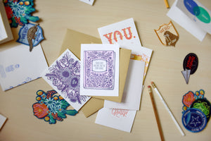 Three letterpressed greeting cards are sitting on top of each other, the top one features a story book wedding card and below it is a card with a thank you bouquet on it.