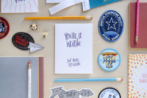 "A letterpressed greeting card that says, ""you're a weird, but you're my weird"" surrounded by a cold pizza club patch, a glow in the dark stargazer patch, and a few pencils."