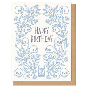 "Greeting card with kraft paper envelope. ""Happy birthday"" hand written in serif font, centered. Surrounded by light blue leaves and skulls with hourglass at bottom."