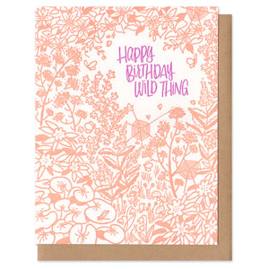 "Greeting card and kraft paper envelope. Reads, ""happy birthday wild thing"" in whimsical, purple, handwritten font. Surrounded by illustration of a dense, wild garden of flowers, leaves and a few spiders."