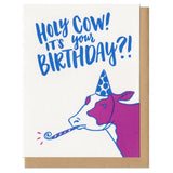 "greeting card and kraft paper envelope. Hand-written text in blue reads, ""Holy cow! It's your birthday?!"" above illustration of cow in party hat with noise maker."