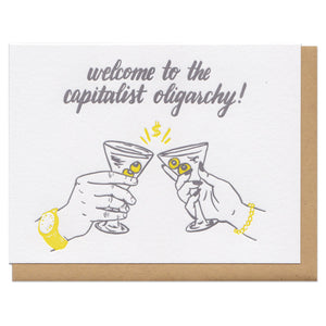 "white greeting card with an illustration of two hands cheers-ing martini glasses beneath grey text that reads ""welcome to the capitalist oligarchy!"""