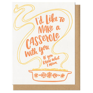 "Greeting card and kraft paper envelope. Illustration of vintage Pyrex casserole dish with handlettered type in the steam that reads ""I'd like to make a casserole with you, If you know what I mean."" In shades of orange."