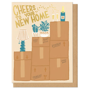 "Greeting card and kraft paper envelope. Card reads, ""cheers to your new home."" Illustration of moving boxes stacked on each other with a lamp and two plants. On the tallest box is a champagne bottle and two champagne flutes."