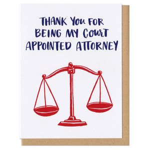 "white greeting card that reads ""thank you for being my court appointed attorney"" in navy above a red illustration of old school scales"