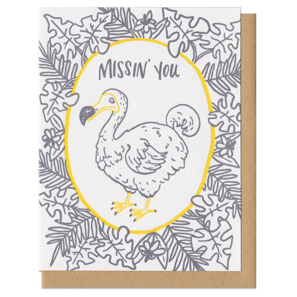 Greeeting card and kraft paper envelope. Grey, illustrated tropical leaves surrounding dodo bird with text above him that reads,