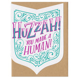"A shield shape die-cut greeting card with kraft paper envelope. Festive hand-drawn text that reads ""huzzah! you made a human!"" in purple and teal, surrounded by teal flourishes."