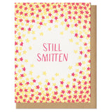"greeting card with a red and yellow star patter surrounded hand-letterinf that reads ""still smitten"""