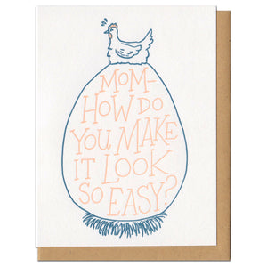 "white greeting card featuring a blue illustration of a hen sitting atop an extremely large egg. orange hand-lettering on the egg reads ""mom - how do you make it look so easy?"""