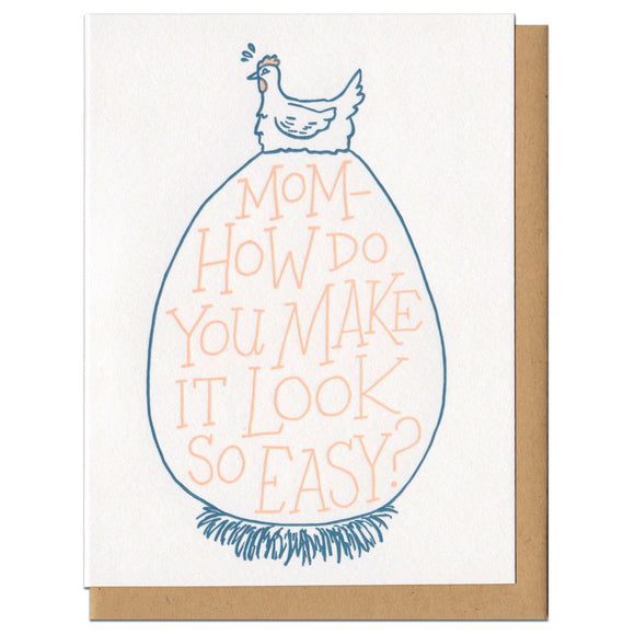 white greeting card featuring a blue illustration of a hen sitting atop an extremely large egg. orange hand-lettering on the egg reads