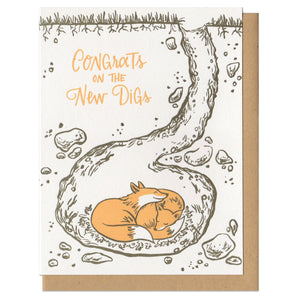 "Greeting card and kraft paper envelope. Text reads ""Congrats on the new digs."" Illustration of cross section of the earth, with a fox den. Two foxes snuggling in their underground den."