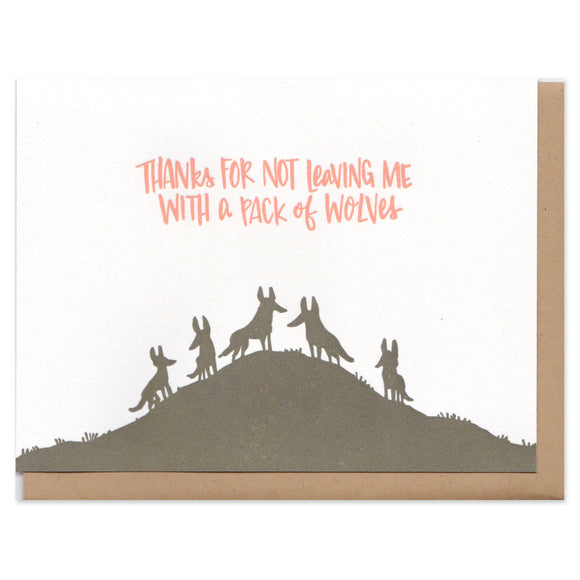 white greeting card with an illustrated silhouetted pack of wolves beneath orange text that reads