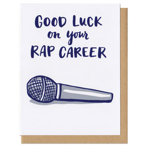 "Greeting card and kraft paper envelope. Card reads in handwritten font, ""good luck on your rap career."" Illustration below of microphone."