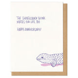 "Greeting card and kraft paper envelope. Purple hand written text reads, ""The shingleback skink mates for life, too. Happy Anniversary!"" Illustration below of disgruntled shingleback skink."