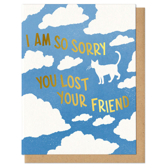 blue greeting card with a white cloud pattern featuring the silhouette of a cat. gold foil stamped lettering reads