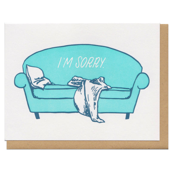 white greeting card featuring an illustrated teal couch with a pillow and blanket slumped on it. white text on the couch reads