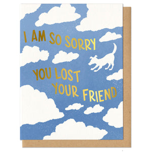 "blue greeting card with a white cloud pattern featuring the silhouette of a dog. gold foil stamped lettering reads ""i am so sorry you lost your friend"""