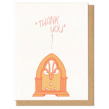 "white greeting card with an illustrated old fashioned radio, printed in orange, beath hand-lettering that reads ""thank you"""