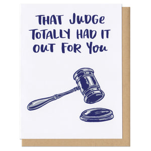 "white greeting card with navy text that reads ""that judge totally had it out for you"" above an illustration of a gavel"