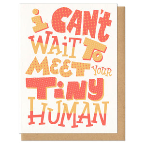 "Greeting card with kraft envelope. Card reads ""I can't wait to meet your tiny human"" in hand-drawn festive block letters in various sizes and patterns in yellow and orange."