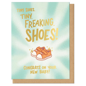 "Greeting card with kraft envelope that reads, ""tiny shoes. tiny. freaking. shoes! congrats on your new baby!"" Letters are in gold foil. Illustration of tiny converse-like baby shoes in peach with light radiating from them."