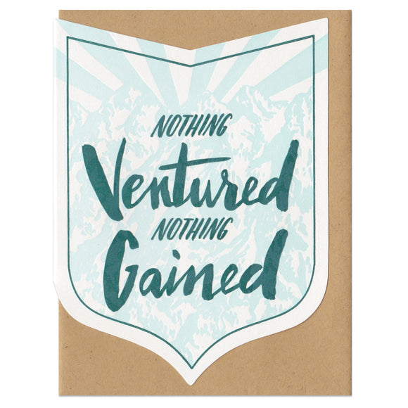 badge-shaped greeting card with a light blue illustration of a mountain range behind green hand-lettering that reads