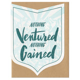 "badge-shaped greeting card with a light blue illustration of a mountain range behind green hand-lettering that reads ""nothing ventured nothing gained"""