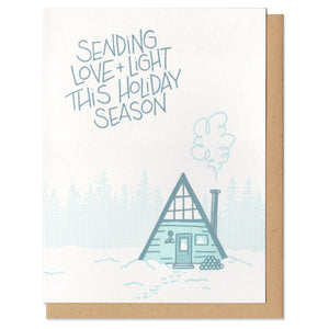 "white greeting card with a blue and teal illustration of an a-frame cabin and tree line of pines. hand lettering above the house reads ""sending love + light this holiday season"""