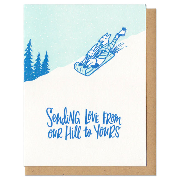 white greeting card with an illustration of a wolf and rabbit dressed for winter, sledding down a hill by silhouetted pine trees. blue hand-lettering beneath them reads