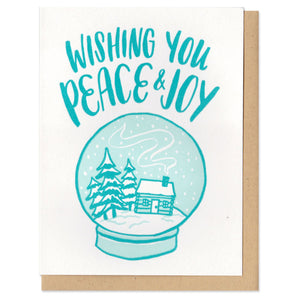 "white greeting card that reads ""wishing you peace & joy"" and features an illustration of a house and trees in a snow globe"