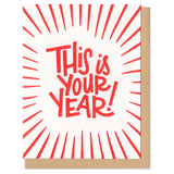 "white greeting card with red lines and hand-lettering that reads ""this is your year!"""