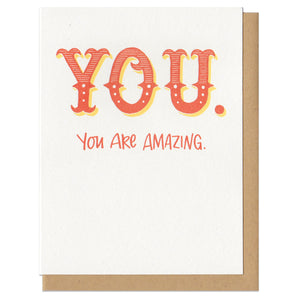 "white greeting card with red hand lettering which reads ""YOU. You are amazing."""