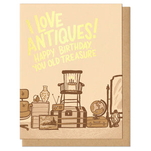 "Greeting card and kraft paper envelope. Hand-written block letter text in gold foil reads, ""I love antiques! Happy birthday you old treasure."" Illustration in sepia tones below it of assorted antiques with a birthday cake."