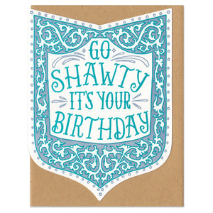 "Die-cut shield-shape greeting card and envelope. Card reads ""go shawty it's your birthday"" in ornate, hand written, blue type. Surrounded by an ornate border in shades of blue."