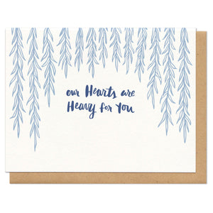 "white horizontal greeting card with light blue illustrated dangling willow branches with navy hand-lettering that reads ""our hearts are heavy for you"""