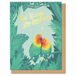 "Text in gold foil in handwritten cursive lettering, ""Best wishes, you lovebirds."" Pair of lovebirds snuggling with gold heart above them, surrounded by lush, tropical greens."