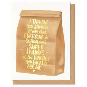 "Greeting card and kraft paper envelope. Illustration of brown paper bag with text on it in gold foil that reads, ""I thought you should know that everyone in school was super jealous of the lunches you packed for me."""