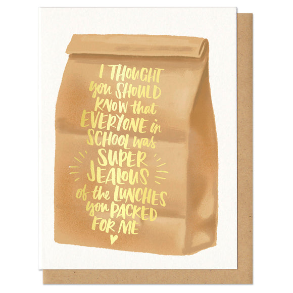 Greeting card and kraft paper envelope. Illustration of brown paper bag with text on it in gold foil that reads,